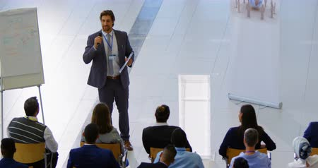 głośniki : High angle view of a Caucasian male speaker standing near a clipboard and speaking to the public in the business seminar 4k