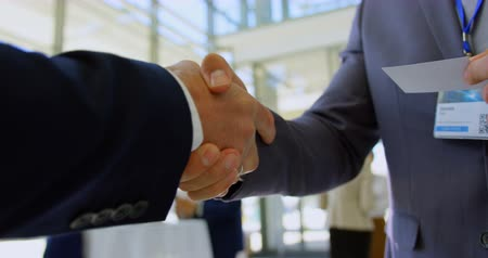 section : Mid section of multi ethnic business people shaking hands with each other during a seminar while holding a visiting card 4k
