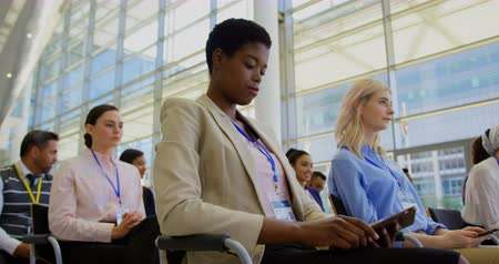 inclusive : Side view of a young African american businesswoman attending a business seminar while using digital tablet 4k