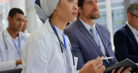 diary : Side view of a female doctor holding a digital tablet while listening at the business seminar 4k