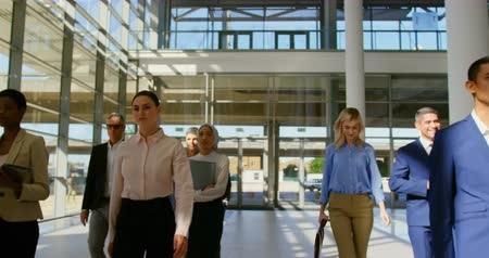 előcsarnok : Front view of multi ethnic business people walking together in the office lobby to attend a business seminar 4k