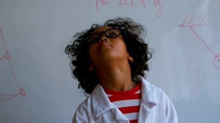 старшей школе : Front view of pretty African-American schoolboy standing in laboratory at school. She is looking up 4k