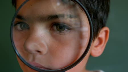 magnifier : Portrait of cute Caucasian schoolboy looking through magnifying glass against green board in classroom. He is looking at camera 4k