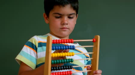 aritmetický : Front view of cute Caucasian boy learning mathematics with abacus against green board in classroom. He is counting beads 4k