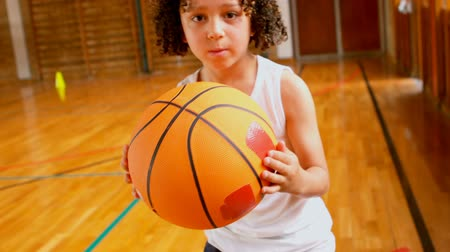 старшей школе : Front view of athletic African American schoolboy standing with basketball in basketball court at school. She is looking at camera 4k