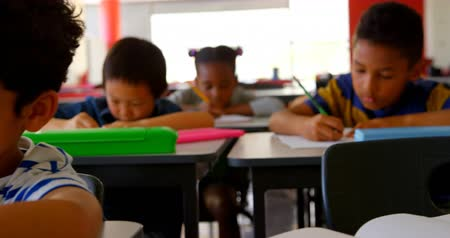 inclusive : Front view of multi-ethnic school kids studying at desk in classroom at school. They are writing on notebook 4k Stock Footage