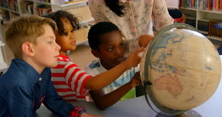 умный : Front view of young pretty Asian female teacher teaching the kids about the globe at table in school library. They are looking at globe 4k