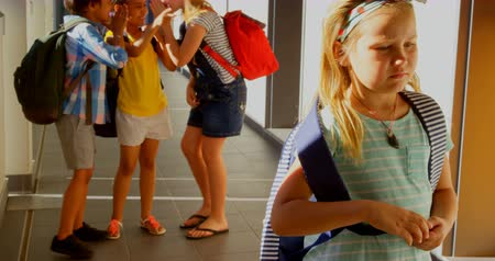 spolužáci : Front view of group of diverse schoolkids bullying sad Caucasian girl in corridor of elementary school. Caucasian girl covering her face with hands 4k