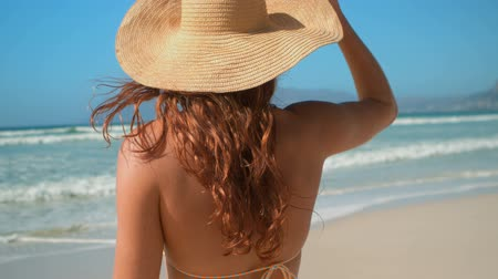desviando o olhar : Rear view of young Caucasian woman in bikini and hat standing on beach in the sunshine. She is looking away 4k