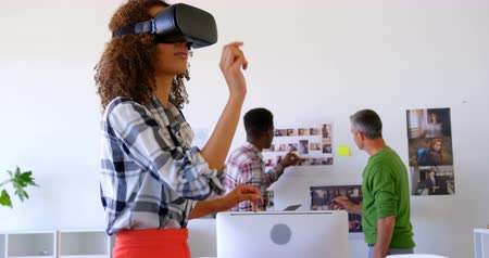 sofisticado : Side view of pretty mixed-race female executives using virtual reality headset in modernoffice. Multi-ethnic coworkers working in the background 4k