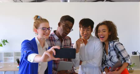 sofisticado : Front view of young multi-ethnic business colleagues taking selfie with mobile phone in modern office. They are smiling and posing 4k Stock Footage