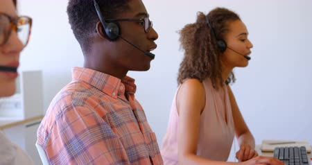 personal computers : Side view of young multi-ethnic customer sales executives talking on headset in modern office. They are working together at desk 4k Stock Footage