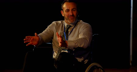 inclusive : Front view of mature Caucasian disabled businessman speaking in business seminar in auditorium. He is sitting on wheelchair and gesturing 4k
