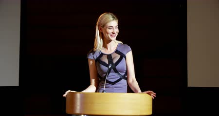 подиум : Front view of young blonde  Caucasian businesswoman speaking in business seminar at auditorium. She is looking and smiling 4k