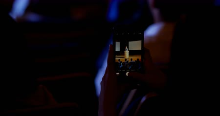 theater hall : Rear view of businesswoman recording lecture during business seminar in auditorium. She is using mobile phone 4k