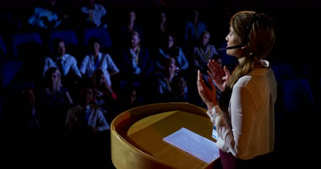 подиум : Side view of young Caucasian businesswoman speaking in business seminar in auditorium. Audience listening her 4k
