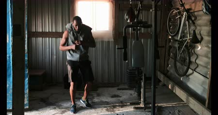 átlyukasztás : Front view of young African American male boxer practicing boxing in fitness studio. He is punching the air 4k Stock mozgókép