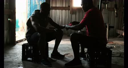 instrutor : Side view of mature African American male trainer assisting young African American boxer in wearing hand wrap in gym. Male boxer preparing for training 4k