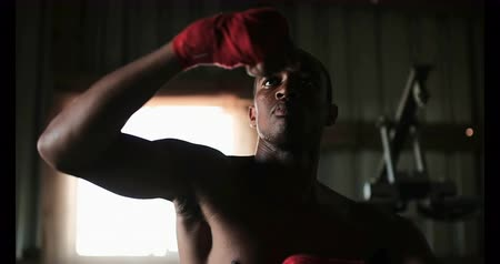 életerő : Front view of young African American male boxer practicing boxing in fitness studio. He is hitting punching bag 4k