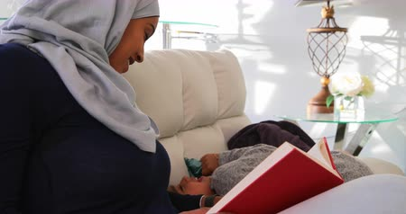 bochechudo : Side view of a young Asian mother wearing a hijab and reading a book while her daughter having fun and relaxing on the sofa in the living room 4k