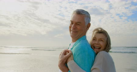 active ageing : Side view of an active senior Caucasian couple having fun and embracing each other while looking away on the beach 4k