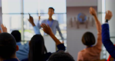 inclusive : Rear view of multi ethnic business people raising their hands for ask a question to the male speaker in the business seminar 4k