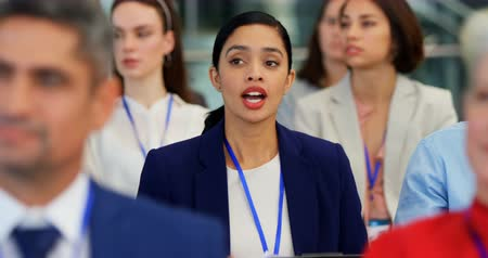 rehberlik : Front view of a mixed-race businesswoman interacting with the speaker while sitting in the business seminar 4k