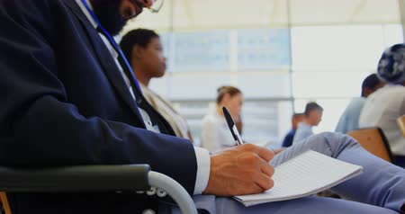 inclusive : Side view of a mixed race businessman writing on his notepad while attending a business seminar 4k