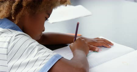 weisheit : Side view of American african drawing a sketch on notebook in the classroom. He is sitting on desk 4k