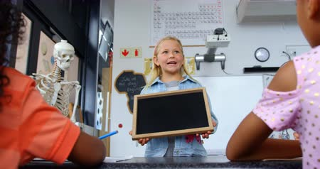 schoolkid : Front view of Caucasian schoolgirl teaching schoolkids in the classroom. She is holding a slate 4k