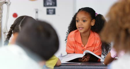 fele olyan hosszú : Front view of African American schoolgirl teaching schoolkids in the classroom. She is holding a book 4k