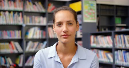 akademický : Front view of Caucasian female teacher standing in the school library. She is looking at camera 4k