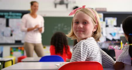 одноклассник : Rear view of happy Caucasian schoolgirl looking at camera in the classroom. Female teacher teaching in the background 4k Стоковые видеозаписи