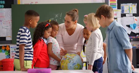 элементарный : Front view of Caucasian female teacher explaining about globe in classroom. Schoolkids looking at globe 4k