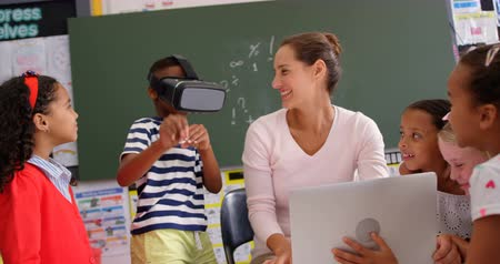 acadêmico : Front view of African american schoolboy using virtual reality headset with teacher and classmates in the classroom. Female teacher using laptop 4k
