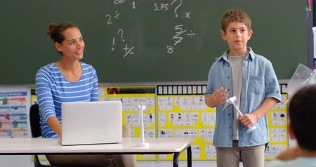 školák : Front view of Caucasian schoolboy explaining about windmill model in the classroom. Schoolkids sitting in the classroom 4k Dostupné videozáznamy