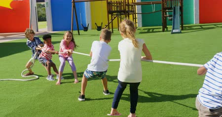 pulling rope : Rear view of mixed-race schoolkids playing tug-of-war in the school playground. They are having fun together 4k
