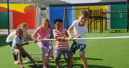 pulling rope : Front view of mixed-race schoolkids playing tug-of-war in the school playground. They are having fun together 4k Stock Footage