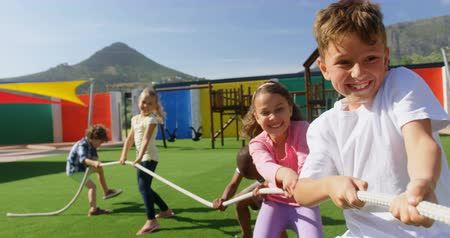 rimorchiatore : Front view of mixed-race schoolkids playing tug-of-war in the school playground. They are having fun together 4k Filmati Stock