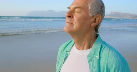 caucasiano : Side view of active senior Caucasian man standing with eyes closed on the beach. Calm sea in the background 4k
