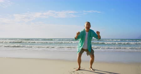active ageing : Front view of active senior Caucasian man jumping on the beach. He is very excited 4k