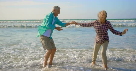 sahil : Side view of active senior Caucasian couple dancing together on the beach. They are having fun 4k