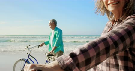active ageing : Active senior Caucasian couple standing with bicycle on the beach. They are interacting with each other 4k Stock Footage
