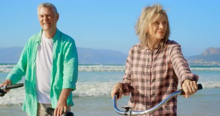active ageing : Front view of active senior Caucasian couple standing with bicycle on the beach. They are smiling and looking away 4k
