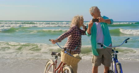 senior citizen : Front view of active senior Caucasian couple taking selfie with mobile phone on the beach. They are standing with bicycle 4k