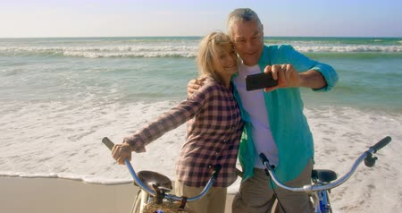 fotografando : Front view of active senior Caucasian couple taking selfie with mobile phone on the beach.They are standing with bicycle 4k