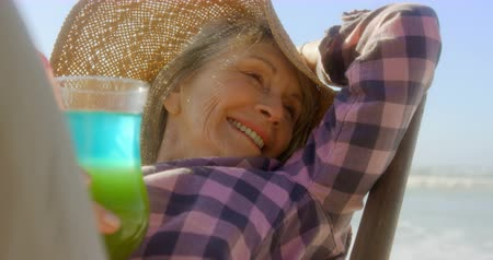 fele olyan hosszú : Front view of active senior Caucasian woman relaxing on a sun lounger at beach. She is drinking cocktail drink 4k