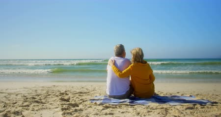 fele olyan hosszú : Rear view of active senior Caucasian couple relaxing on the beach. They are looking at view 4k