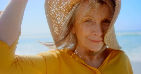 пенсионер : Front view of active senior Caucasian woman in hat standing on the beach. She is smiling and looking at camera 4k