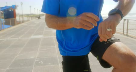kaukázusi : Mid section of active senior man checking time on smartwatch on a promenade at beach. He is sitting on bicycle 4k Stock mozgókép